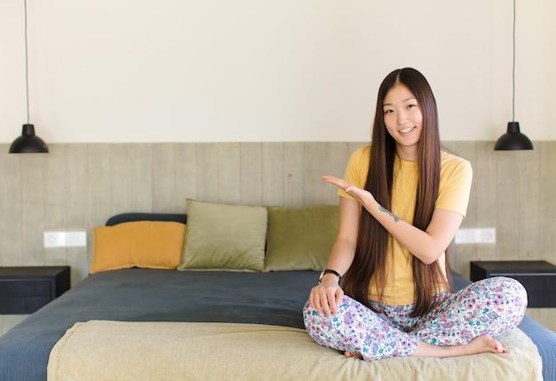 Jovem mulher asiática sorrindo alegremente, sentindo-se feliz e apontando para os lados e para cima, mostrando o objeto no espaço da cópia