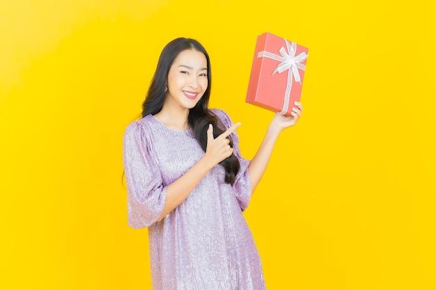 Jovem mulher asiática sorrindo com caixa de presente vermelha em amarelo