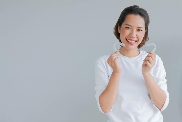 Jovem mulher asiática sorrindo com retentor alinhador dental invisível isolado em fundo cinza