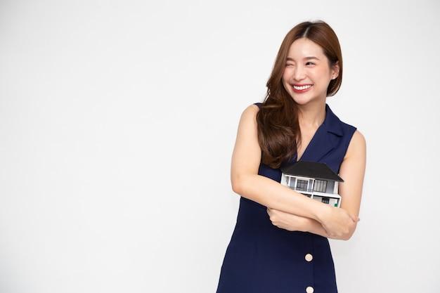 Jovem mulher asiática sorrindo e abraçando o modelo de amostra da casa dos sonhos, isolado sobre fundo branco