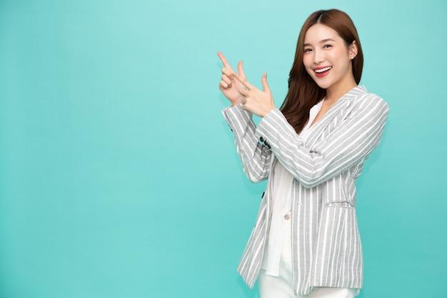 Jovem mulher asiática sorrindo e apontando o dedo para