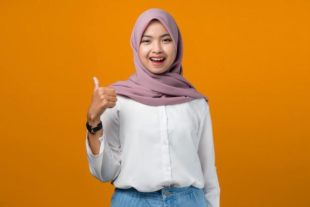 Jovem mulher asiática sorrindo e fazendo sinal de positivo em amarelo