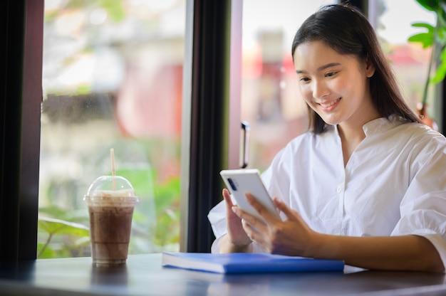 Jovem mulher asiática sorrindo e olhando para o smartphone