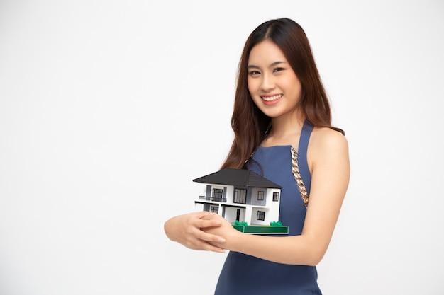 Jovem mulher asiática sorrindo e segurando o modelo de casa.