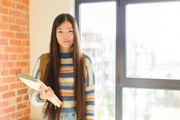 Jovem mulher asiática sorrindo positivamente e com confiança, parecendo satisfeita, amigável e feliz