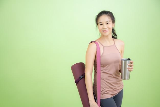 Jovem mulher asiática sorrir alegremente carregando equipamentos de ioga