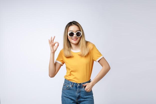 Jovem mulher asiática sorriso bonito com sinal de dedo bem isolado no fundo branco
