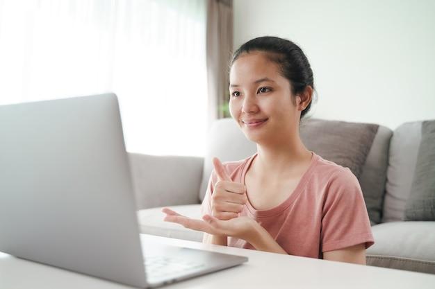 Jovem mulher asiática surda com deficiência usando computador portátil para aprendizagem de chamada de videoconferência online e comunicação em linguagem de sinais.