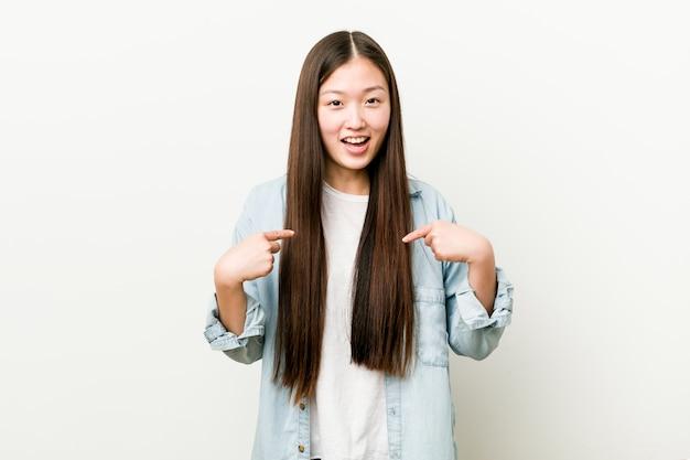 Jovem mulher asiática surpreendeu apontando para si mesmo, sorrindo amplamente.