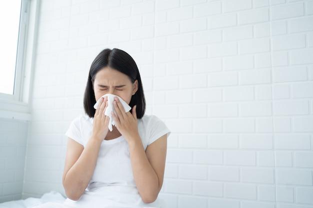 Jovem, mulher asiática, tem, nariz, alergia, gripe, espirrando nariz, sentar-se cama, em, quarto