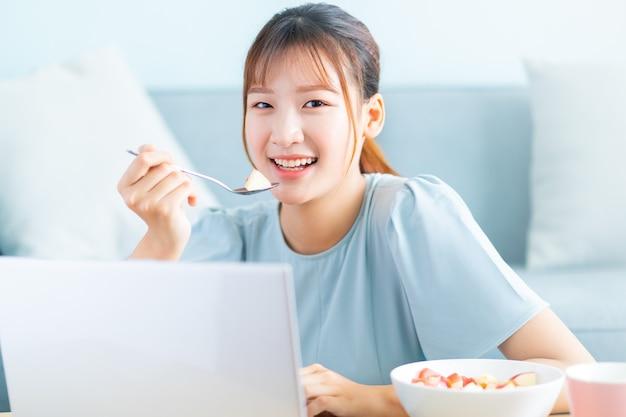 Jovem mulher asiática tomando café da manhã e selfie na sala de estar