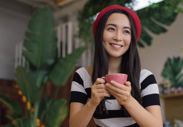 Jovem mulher asiática tomando café no café. retrato de menina hipster positiva segurando a xícara de chá. modelo coreano usando boina vermelha elegante posando para fotos e sorrindo. conceito de coffee-break