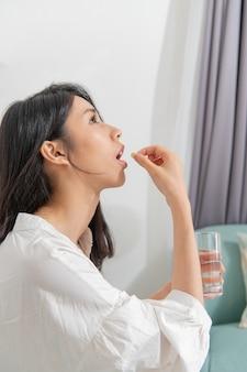 Jovem mulher asiática tomando remédio na sala de estar