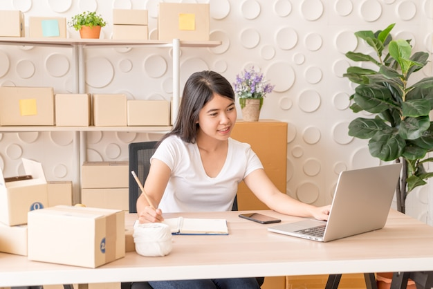 Jovem mulher asiática trabalhando com tablet digital no local de trabalho
