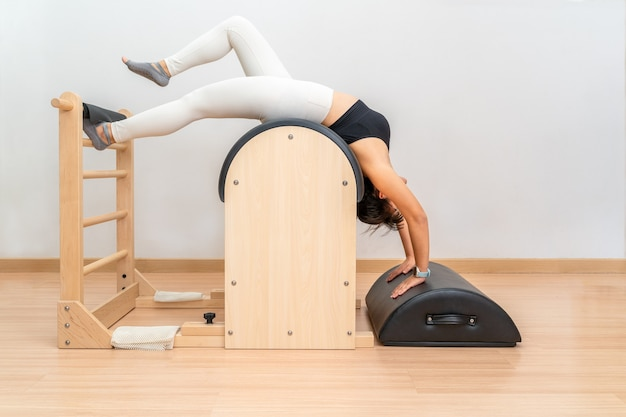 Jovem mulher asiática trabalhando em uma máquina de barril de escada de pilates durante seu treinamento de exercícios de saúde