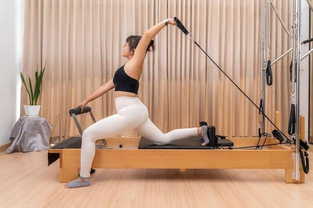 Jovem mulher asiática trabalhando em uma máquina reformadora de pilates durante seu treinamento de exercícios de saúde