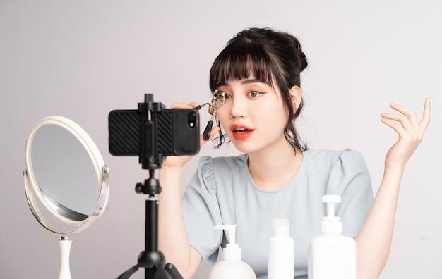 Jovem mulher asiática transmitindo ao vivo para professora de maquiagem online