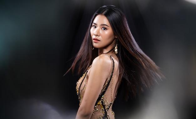 Jovem mulher asiática usa lantejoulas vestido de baile
