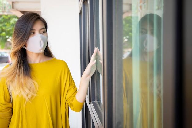 Jovem mulher asiática usa máscaras cirúrgicas para se proteger contra vírus e poeira.