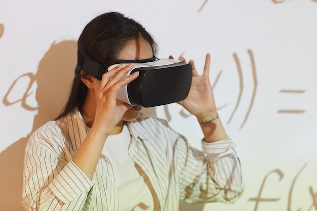 Jovem mulher asiática usando aplicativo de realidade virtual para solução de equações em aula universitária