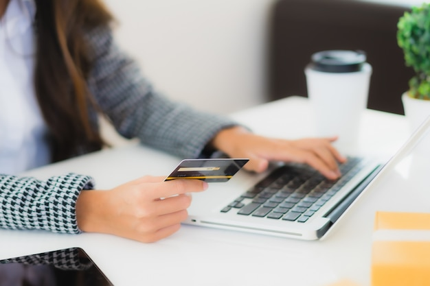 Jovem mulher asiática usando cartão de crédito com o laptop para compras on-line