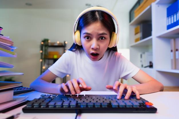 Jovem mulher asiática usando fone de ouvido e a mão levanta os braços e os punhos cerrados com mostra forte e poderoso, comemorando a vitória expressando sucesso.