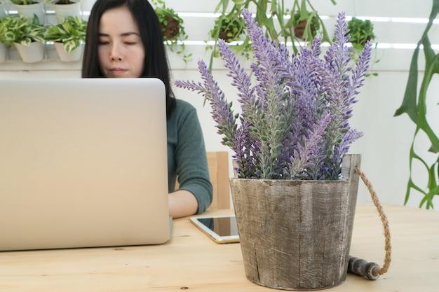 Jovem mulher asiática usando laptop na mesa de madeira
