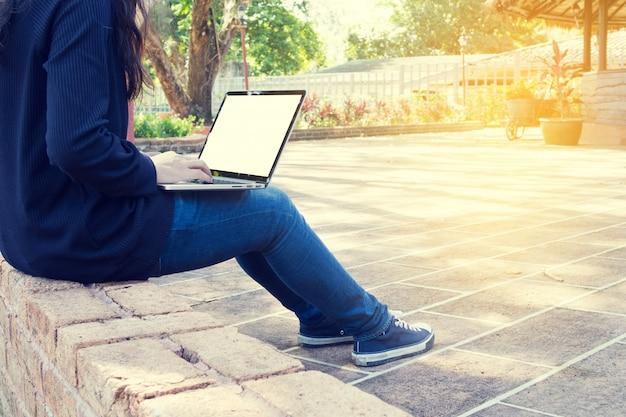Jovem mulher asiática usando laptop no parque.