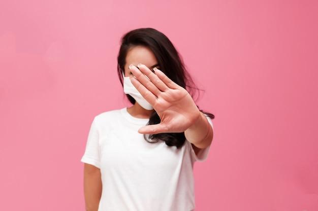 Jovem mulher asiática usando máscara de proteção ou máscara cirúrgica para vírus protegido e poluição do ar, tornando o vírus de parada de mão na parede rosa, conceito de cuidados de saúde e coronavírus