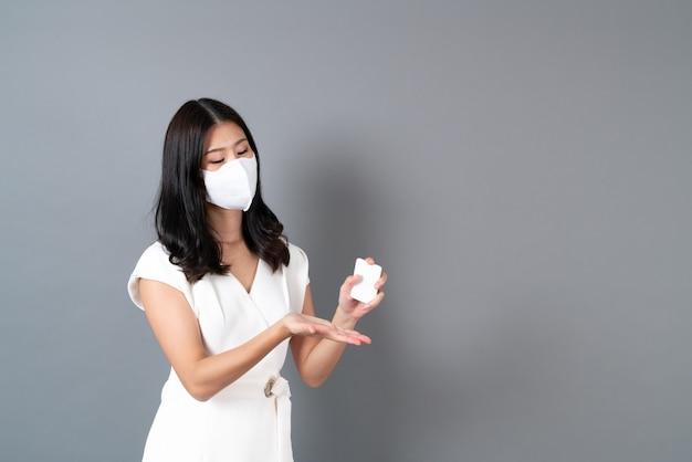 Jovem mulher asiática usando máscara e usando álcool em spray para proteger o coronavírus em cinza