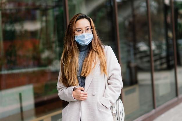Jovem mulher asiática usando máscara facial está de pé em uma rua doméstica. nova epidemia normal de covid-19