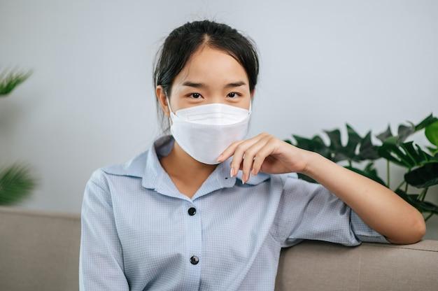 Jovem mulher asiática usando máscara facial sentada no sofá da sala de estar, ela lendo livro durante a quarentena covid-19 auto-isolamento em casa