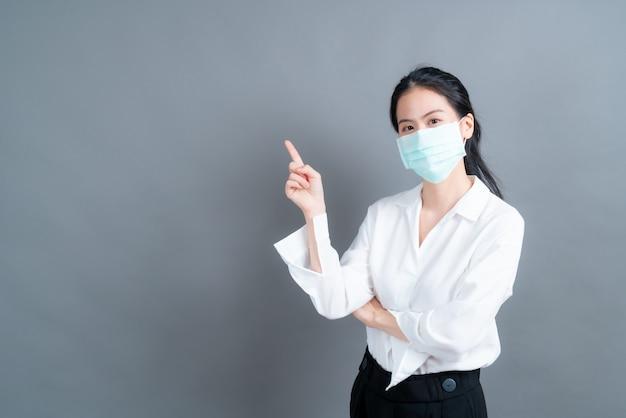 Jovem mulher asiática usando máscara médica e dedo apontando no espaço da cópia
