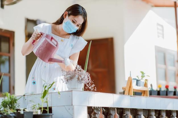 Jovem mulher asiática usando máscara médica em pé regando plantas verdes em casa para auto-quarentena 14 dias após a disseminação de doenças de covid 19