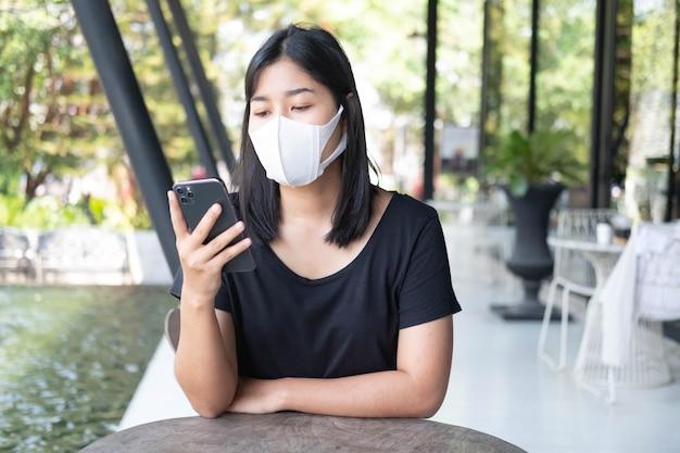 Jovem mulher asiática usando máscara médica usando smartphone em uma cafeteria trabalho à distância social