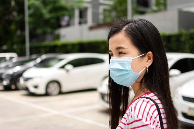 Jovem mulher asiática usando máscara protetora de higiene médica no estacionamento.