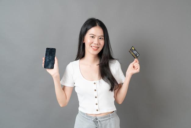 Jovem mulher asiática usando o telefone com a mão segurando um cartão de crédito - conceito de compra online.