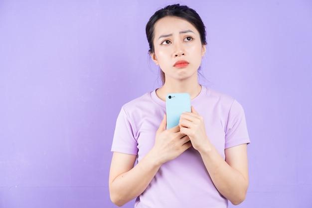 Jovem mulher asiática usando smartphone em fundo roxo