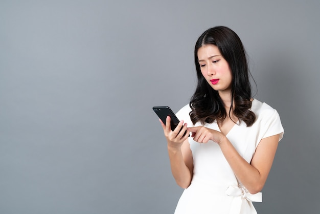Jovem mulher asiática usando telefone com cara de mau humor