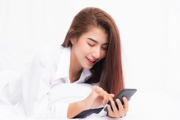 Jovem mulher asiática usando telefone inteligente no quarto em casa feliz e sorrir.