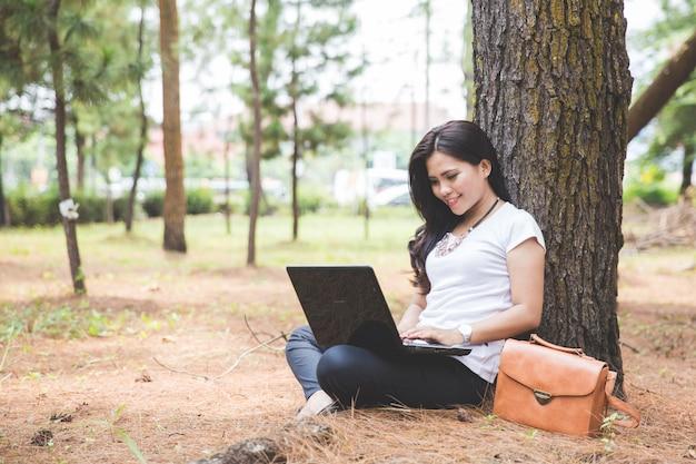 Jovem mulher asiática usando um laptop enquanto está sentado ao ar livre em um parque