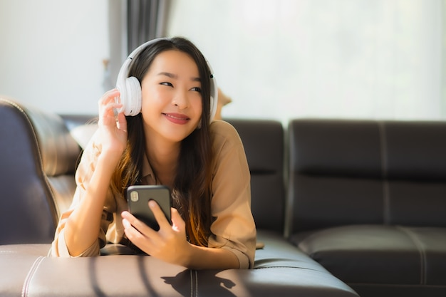 Jovem mulher asiática usar smartphone no sofá com fones de ouvido