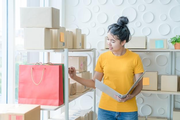 Jovem mulher asiática, verificação de mercadorias na prateleira de estoque em armazém