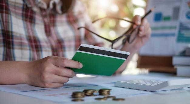 Jovem mulher asiática, verificando contas, impostos, saldo de conta bancária e cálculo de despesas de cartão de crédito. conceito de despesas familiares.