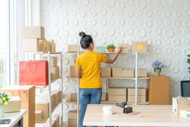 Jovem mulher asiática verificando mercadorias na prateleira de estoque no armazém - venda on-line ou compras on-line conceito