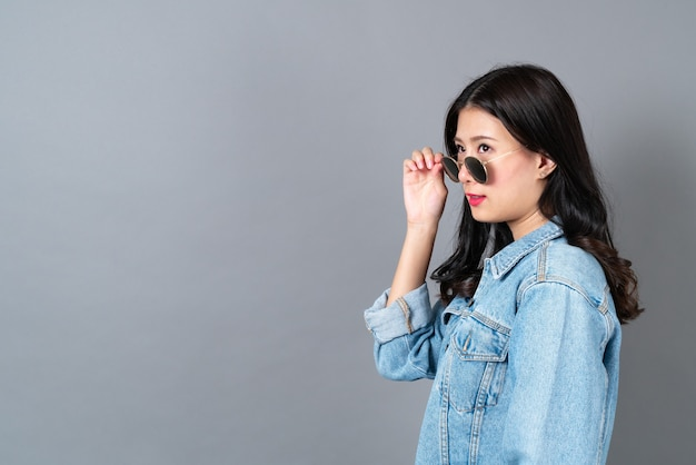 Jovem mulher asiática vestindo jaqueta jeans e óculos escuros cinza com espaço de cópia