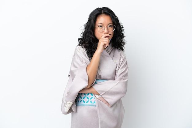 Jovem mulher asiática vestindo quimono isolado no fundo branco, tendo dúvidas e com expressão facial confusa