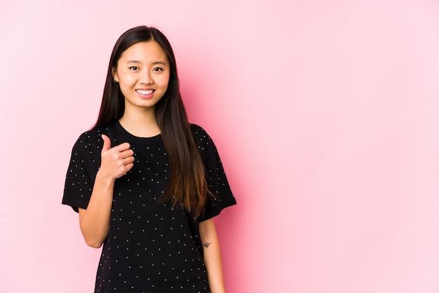 Jovem mulher asiática, vestindo roupas elegantes, sorrindo e levantando o polegar