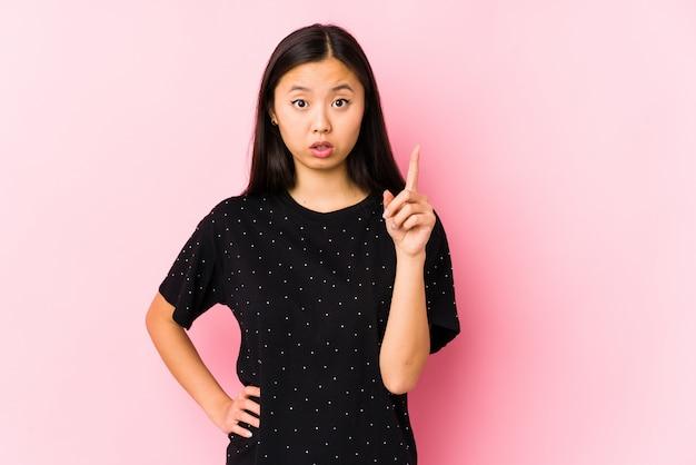 Jovem mulher asiática, vestindo roupas elegantes, tendo uma idéia