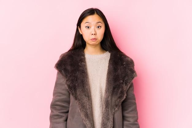 Jovem mulher asiática vestindo um casaco encolhe os ombros e abre os olhos confusos